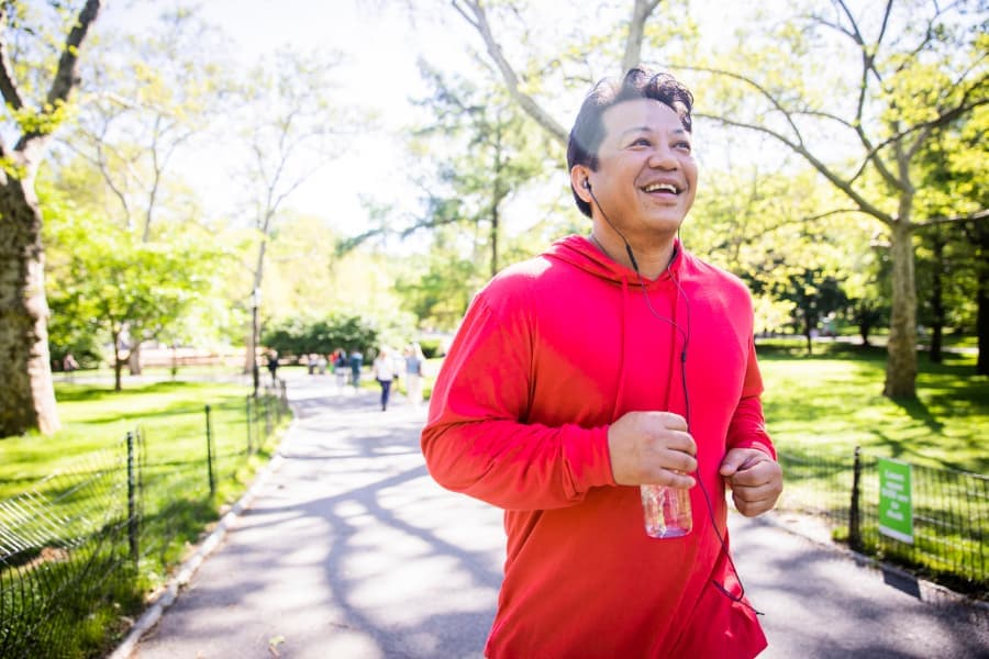 Man running outdoors in sunny weather