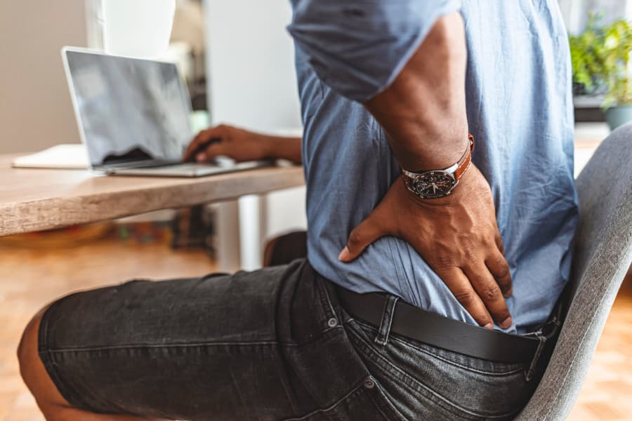 Man sitting and rubbing back in pain